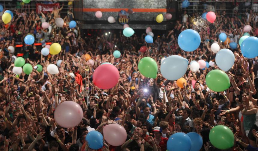 A crowd of students has balloons dropped on them during their grad tip to Cancun